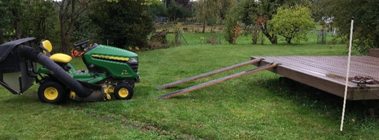 Photo of lawn mower being loaded onto trailer